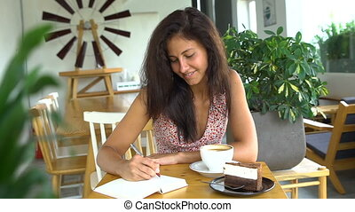 Young woman writing diary in her journal and drink coffee in...