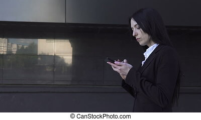 Business woman walking and using a smartphone