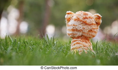 Plush Toy Cat Sitting in Green Grass - Plush toy cat sitting...