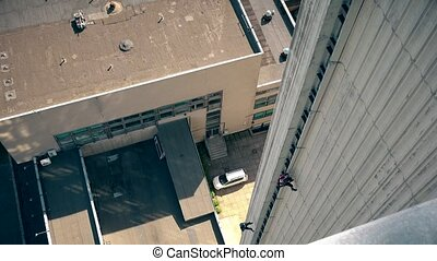 Two sportsmen men descend down from high skyscraper house wall