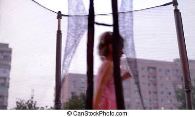 Bouncing Around Trampoline Little Girl At Sunset - Bouncing...