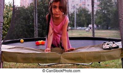 Little Girl On Trampoline At Sunset - Little girl on...