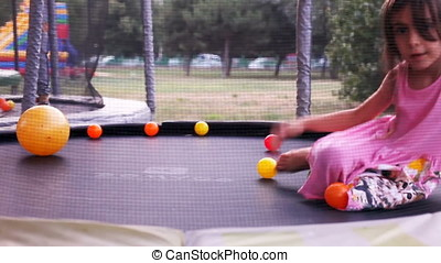 Little Girl Resting And Jumping On Trampoline At Sunset -...