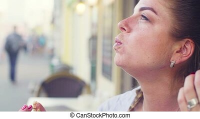 Portrait of young woman eating cookie - Close up Portrait of...