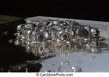 Transparant gelly balls on a mirror with water shining in...