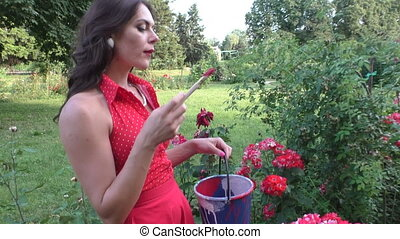 Woman is painting flowers. - Young Woman Painting Flowers In...
