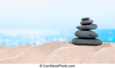 On the Beach - balanced stones arranged on a sand dune in front of beautiful azure sea - seamless loop - ProRes