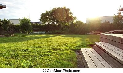 summer garden mown lawn and wooden terrace stairs -...