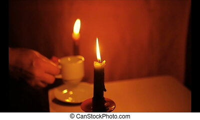 Two burning candles, a cup of coffee and a vase with roses....