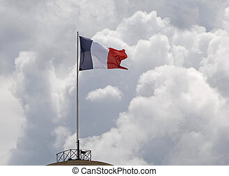 French flag on flagstaff in Paris against clouds