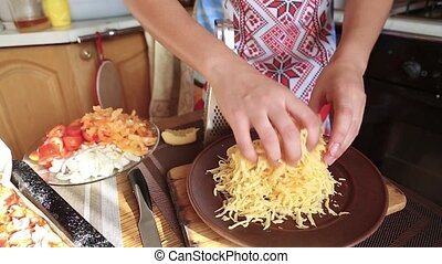 Grated cheese in a plate, women's hands touch the shabby...