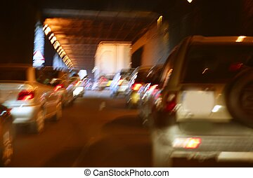 Cars moving traffic with brurred motion headlights on the tunnel