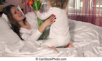 beautiful mother mom get flowers and kiss from her adorable...