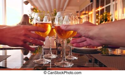 Friends clink glasses with alcohol in a restaurant by the...