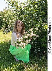 girl near a flowering bush - Slender girl in a summer park...