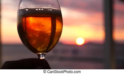 A man is holding a glass of alcohol against the sunset over...