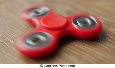 Red fidget spinner spinning on a wooden table. Close up.