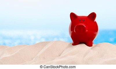 On the Beach - piggy bank on a sand dune in front of...