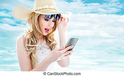 Closeup portrait of a young blonde using a smartphone -...
