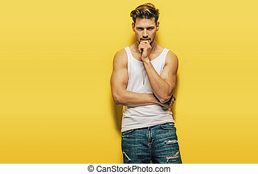 Handsome, muscular man posing on a yellow background