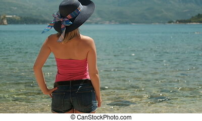 Young woman standing on beach in sunny afternoon.