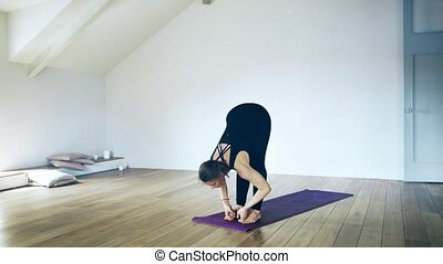 Portrait of a beautiful woman in black doing yoga indoors