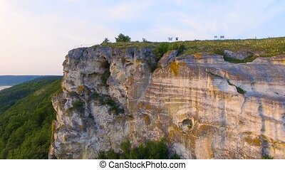 Aerial shot of a sunset near rocks. Vivid colors are...