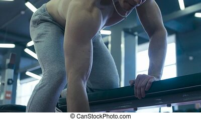 Very strong man lifting dumbbells in fitness studio