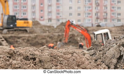 Builders work into large clay pit for construction