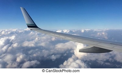 Wing of an airplane flying above the clouds. People look at...