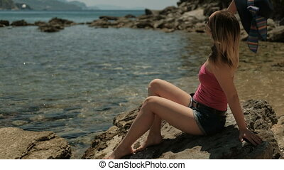 Young lady sits on coastline on summer day. Quietly located...
