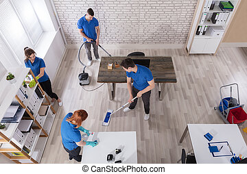 Elevated View Of Janitors Cleaning The Office - Elevated...