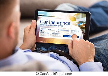 Man Filling Car Insurance Form On Digital Tablet