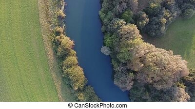Bird view of following river surrounded with fields. Aerial...