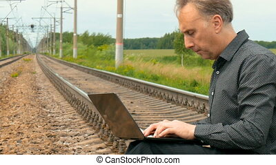 A man is sitting on the rails and writing a letter on the...