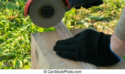 The worker cuts the metal threshold for the door by grinder....