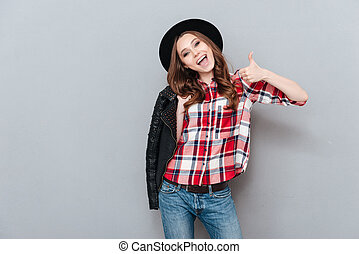 Excited stylish woman in plaid shirt showing thumbs up...
