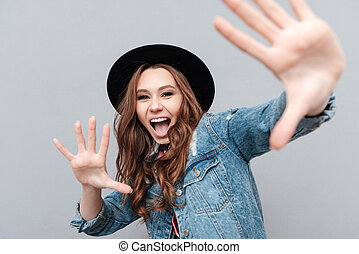 Close up portrait of a cheerful young woman in hat