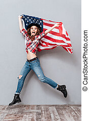 Happy excited young woman holding USA flag and jumping -...