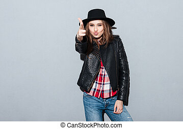 Woman in hat and leather jacket shoots from improvised gun -...