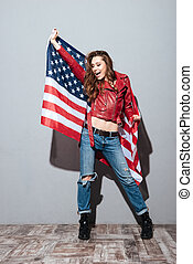 Patriotic girl wearing red leather jacket and holding USA...