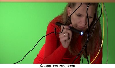 Business woman trying to repair computer with flash light...