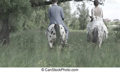 Happy bride and groom on horseback in the forest, true love, beautiful nature