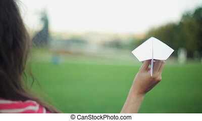 Woman holding a paper airplane