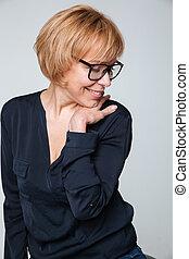 Vertical image of smiling elderly woman posing in studio -...