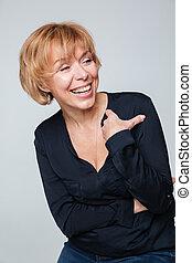 Vertical image of laughing elderly woman posing in studio -...