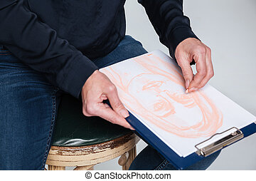 Cropped image of elderly woman drawing on clipboard