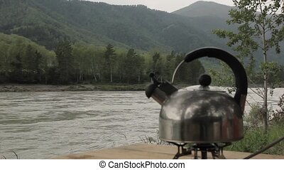 kettle boils on fire on a river background