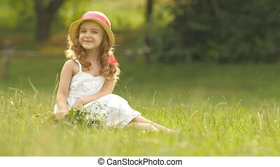 Baby sits on a glade in a sarafan and hat, holds wild...