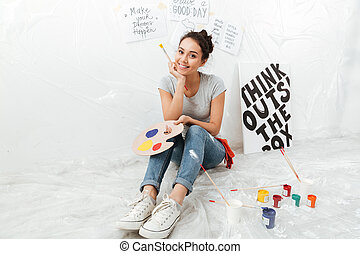 Happy young lady artist sitting on floor - Image of happy...